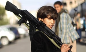 A Yemeni boy holds an assault rifle. Other prizes include a motorcycle and a laptop.