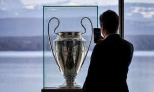 A man takes a picture of the Champions League trophy displayed at Uefa's headquarters in Nyon.