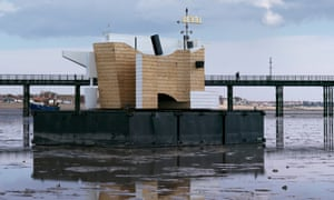 Flood House, a floating weather station, at low tide in front of a pier