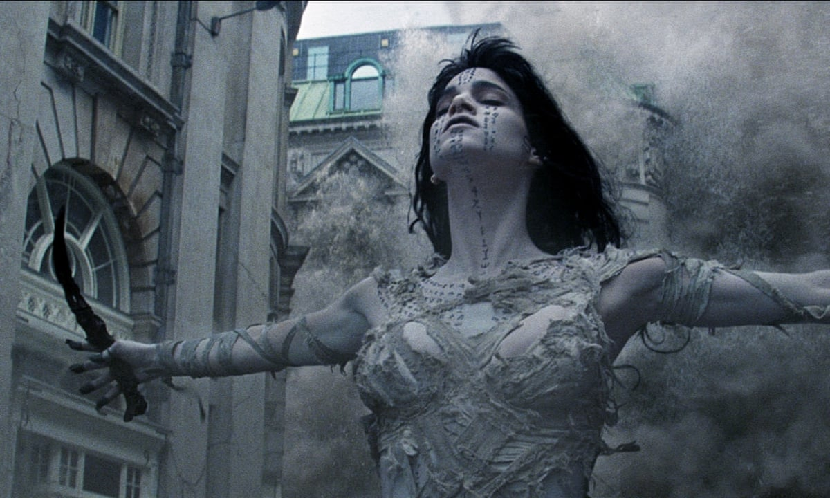 This image is from The Mummy (2017). Ahmanet throws her arms out wide as a building explodes behind her.