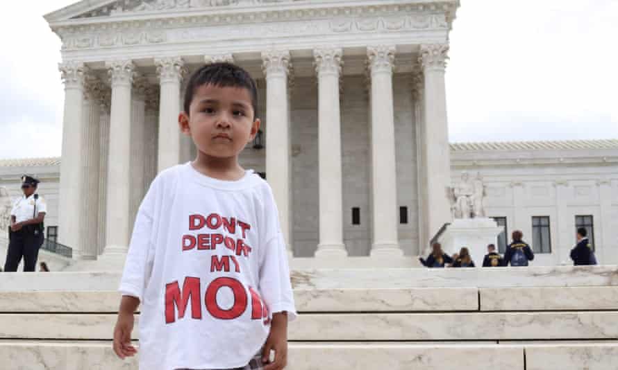 A boy wears a T-shirt reading 'Don't deport my mom.