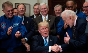 Donald Trump shakes Buzz Aldrin's hand after signing an executive order about space exploration.