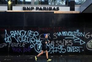 A man jogs past a vandalised bank