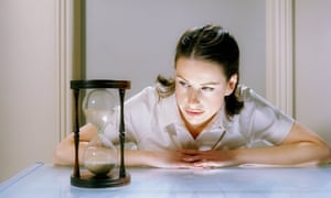 Staged picture of a woman watching sand in an hourglass