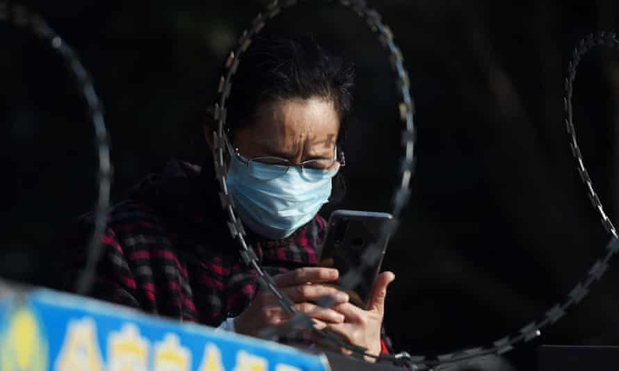 A woman uses her mobile phone behind barbed wire at an entrance of a residential compound in Wuhan