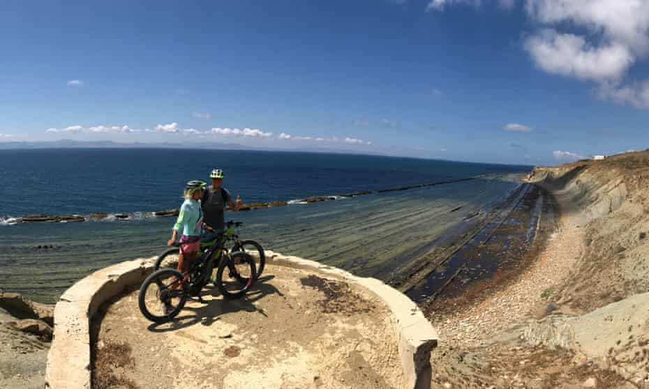 couple on ebikes with coastal view