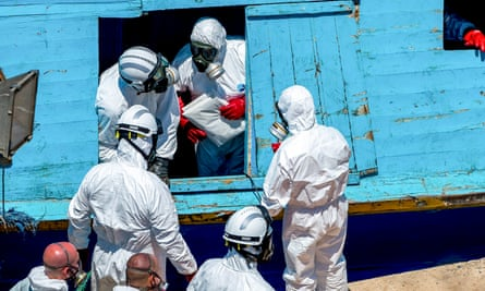 Army staff remove bodies from a fishing boat in Malta, July 2014.