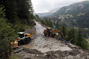 Worker use diggers to clean the road of the nineteenth stage between Saint Jean De Maurienne and Tignes Organizers stopped the stage for the riders' safety when a sudden, violent storm made the route through the Alps too dangerous.