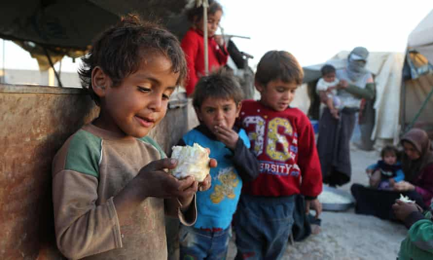 A Syrian child holds a piece of cauliflower at the Ash'ari camp for displaced people in the rebel-held eastern Ghouta area, outside Damascus