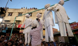 A man beats an effigy of one of the rapists at a protest against three rapes of girls, in Ahmedabad, India.