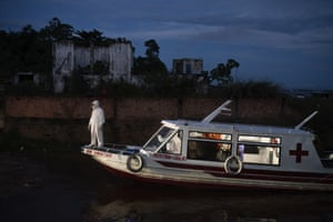 A health worker stands on a boat carrying Covid-19 patient Jose da Conceição as he waits for an ambulance to transfer him to a hospital after arriving at the port of Manacapuru.