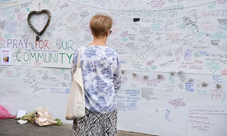 A woman reads a wall of tributes close to Grenfell Tower in west London.