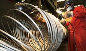 A worker polishes steel coils at a factory in Dalian in China.