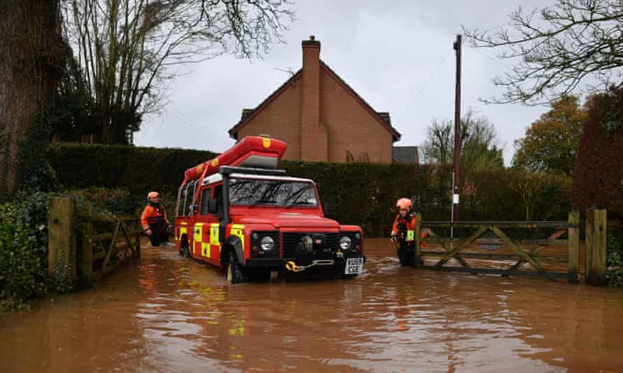 Hereford Fire and Rescue personnel drive into a property cut off by flooding in the village of Hampton Bishop in Herefordshire.