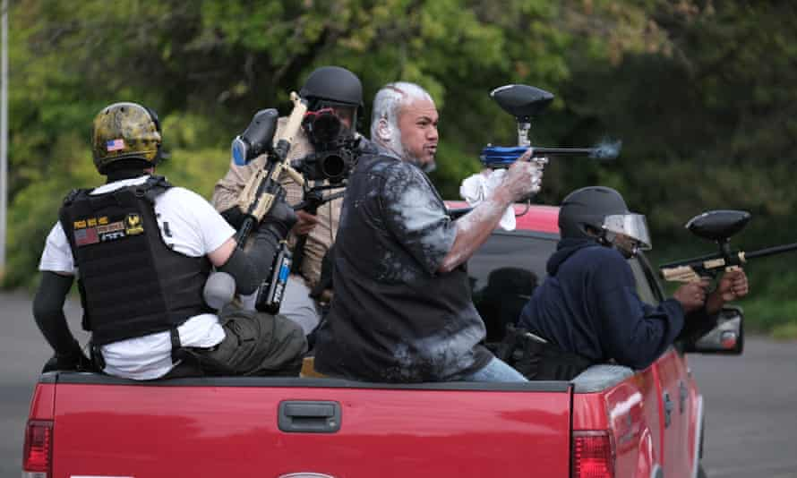 Tusitala 'Tiny' Toese, a member of the far-right group Proud Boys, fires paintball rounds at anti-fascist protesters as they depart from their rally on Sunday in Portland.