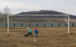 Children play with a puppy near a goalpost on a football pitch in the Siberian settlement of Novosyolovo, Krasnoyarsk region