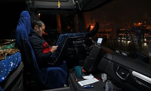 A Romanian driver puts his feet up inside his cab while parked at a truck stop off the M20 leading to Dover.