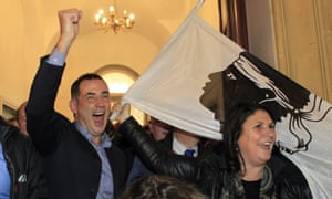 Gilles Simeoni (left), the mayor of Bastia and leader of the nationalists, celebrates victory in the French regional elections next to a Corsican flag.
