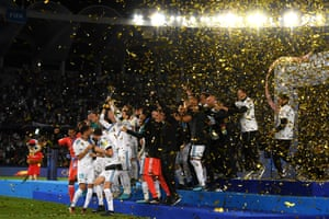 The Real Madrid players celebrate with the trophy under a flurry of shiny ticker-tape.