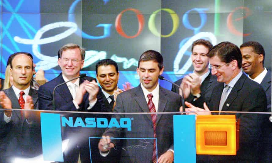 Co-founder Larry Page (centre, writing) and other bosses at Google's 2004 flotation.