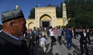 Uighur men dancing after Eid al-Fitr prayers, marking the end of Ramadan, outside the Id Kah mosque in Kashgar, in China's western Xinjiang region