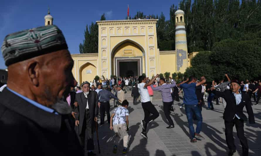 Members of the Muslim ethnic minority Uighur group dance after Eid al-Fitr prayers, outside the Id Kah mosque in Kashgar, in China's western Xinjiang region. Chinese authorities have cracked down on the expression of Uighur culture and Muslim faith in the region.