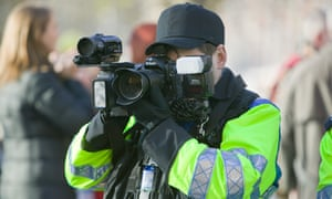 A police photographer takes images of protesters at a climate change rally in London, December 2008.