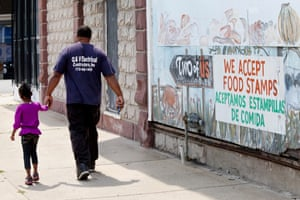 A sign painted on top of a mural says 'We accept food stamps,' in Harvey, Illinois.