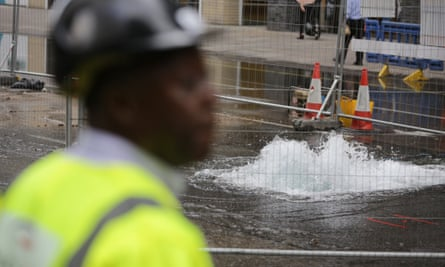 A maintenance worker stands in front of a burst water main in London