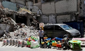A street vendor sells toys next to rubble of damaged buildings in the city of Idlib.