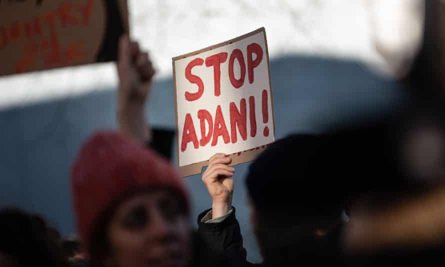 A hand holds up a 'Stop Adami' sign