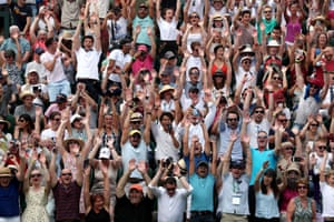 The crowd on court 3 perform a mexican wave as they wait for the tennis to start.