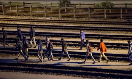 Migrants walk along railway tracks at the Eurotunnel terminal in July 2015 at Calais-Frethun.
