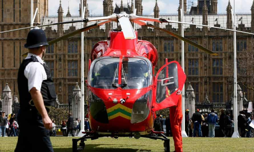 A police officer stands next to an air ambulance helicopter at Parliament Square in central London