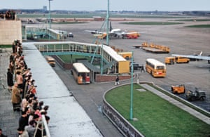 In 1959 no covered walkways were attached when the aircraft parked, but glass walkways were provided from the buses or passengers could just walk out to the aircraft.