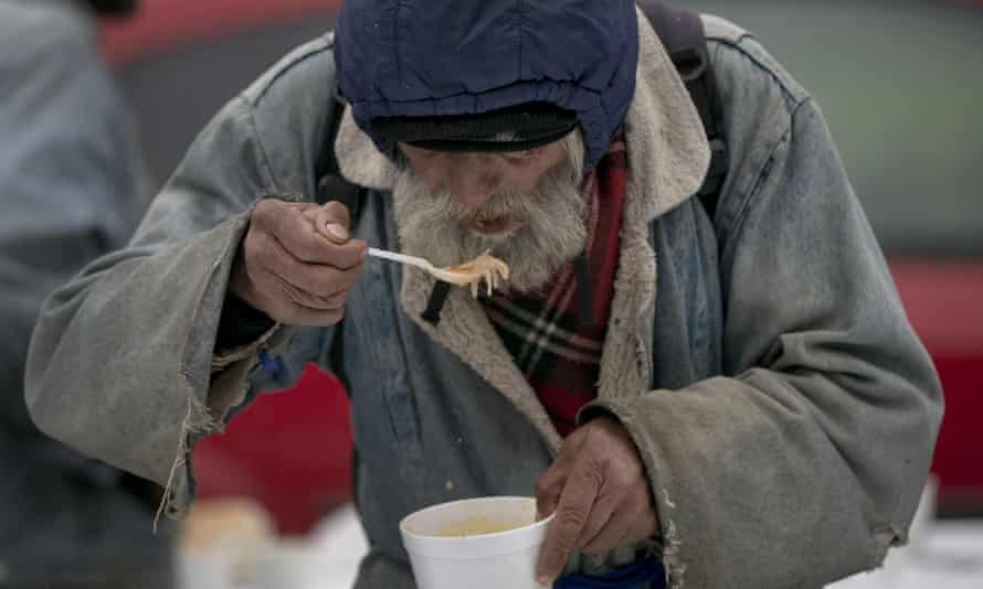 A homeless man eats soup received at a humanitarian event outside the main railway station in Bucharest, Romania