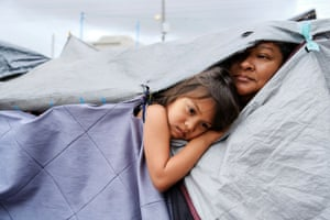 Honduran migrants Kami and her aunt Mariana listen as other migrants discuss hygiene at a makeshift camp at the El Chaparral border port of entry with the US.