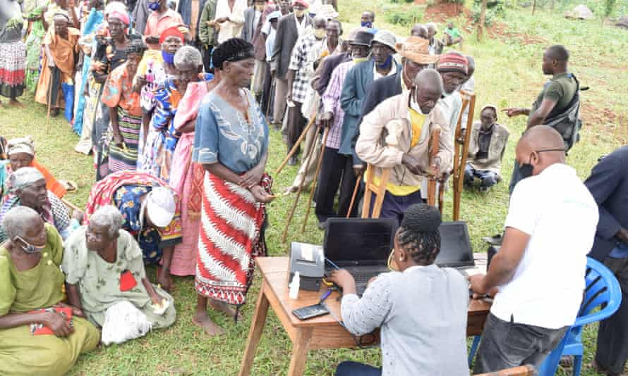 Elderly people wait to validate their identity cards