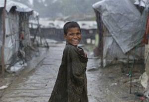 A young Rohingya is seen during a rainstorm at the Nayapara refugee camp
