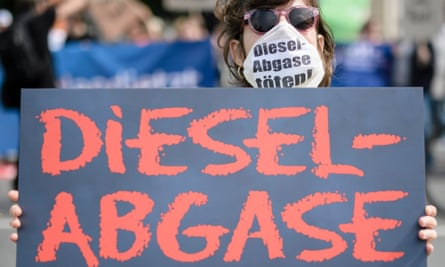 A protester wears a mask and a placard reading 'diesel emissions kill' in front of the German transport ministry in Berlin.
