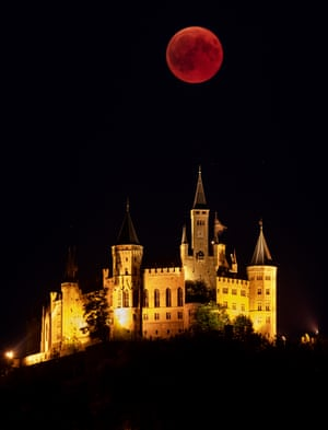 The moon rises above behind The Hohenzollern Castle, in Hechingen, Germany.