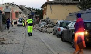 operatori del soccorso e residenti stare su una strada nel Amatrice a seguito del terremoto in Italia centrale.