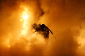 A firefighter tries to extinguish a burning car in France