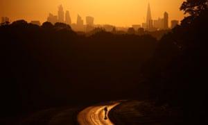 A cyclist rides through Richmond Park in London during sunrise