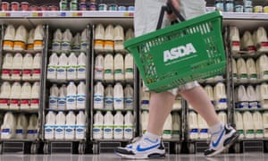 Shopper with Asda basket walking past cartons of milk