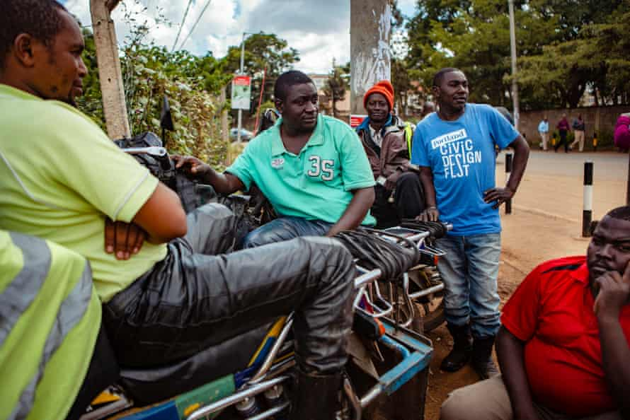Fred Juma waits for business with fellow boda boda drivers in Nairobi