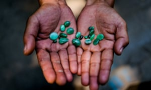 MYITKYINA, MYANMAR - MARCH 13th, 2016: A jade trader displays a selection of his stones for sale.