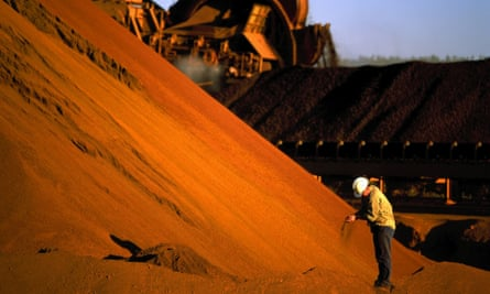 A worker inspecting iron ore stockpiles