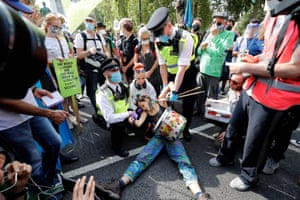 London, UK. Police officers detain an activist from the climate protest group Extinction Rebellion during a demonstration in Parliament Square
