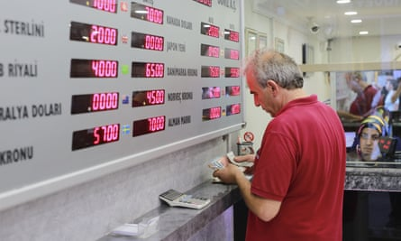 A man counts his liras at a currency exchange shop in Istanbul's market on Friday.